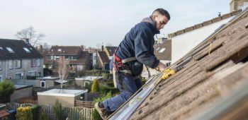 man making the construction for the solar panels high on the roof